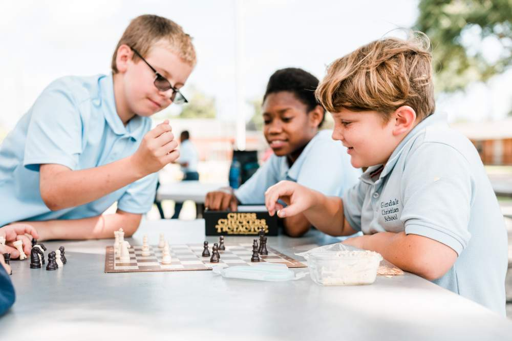 Three young boys playing chess